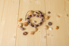 Crochet handmade beads, sea stones and seashells on a wooden tab Stock Photo
