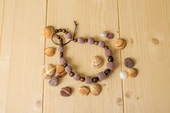 Crochet handmade beads, stones and sea shells on a light wooden Stock Photography