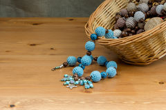 Crochet handmade blue beads on a wooden table Royalty Free Stock Photos
