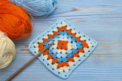 Crochet handmade granny square, a hook and yarn balls. The beginning of bright plaid, blanket. Colorful original crochet handmade. Craft work. Homemade creative royalty free stock photo