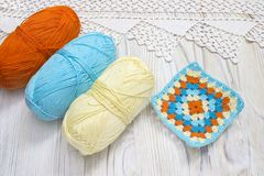 Crochet handmade granny square and yarn balls. The beginning of bright plaid, blanket. Colorful knitted handmade work. Homemade cr. Eative crochet lace pattern royalty free stock photography