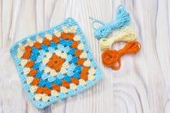Crochet handmade granny square, yarn balls. The beginning of bright plaid, blanket. Colorful original knitted handmade work. Homem. Ade creative crochet pattern Stock Photo