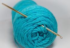 Crochet hook in skein of teal yarn. Gold crochet hook in bundle of teal yarn Royalty Free Stock Images