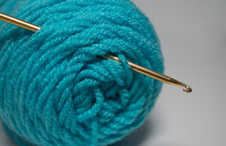 Crochet hook in skein of  yarn. Gold crochet hook in bundle of teal yarn with  background Royalty Free Stock Image