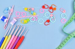 Free Crochet Hooks, Markers, Row Counters And Needles Laid Out In A Mess On A Blue Background. Stock Photos - 212507333