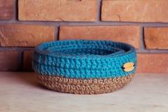 Crochet knitt basket. Hand made basket on brick background Stock Images