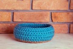 Crochet knitt basket. Hand made basket on brick background Stock Photography