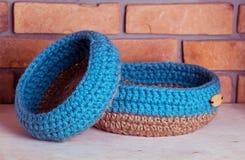 Crochet knitt baskets. Hand made baskets on brick background Stock Images