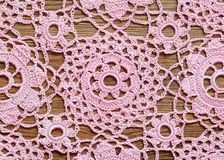Crochet lace on a wooden surface. Pink crochet lace on brown wooden surface Stock Image