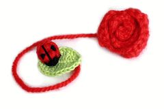 Crochet ladybird on the leaf near crocheted rose Stock Photo