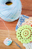 Crochet, the making of a crocheted. On wood background, a retro handmade craft with balls of yarn, color blue Stock Photos