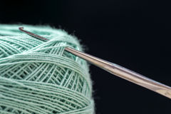 Crochet. Needle and turquoise thread on a dark background Royalty Free Stock Photos