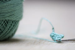 Crochet. Needle and turquoise thread on a light background Stock Image