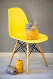 Crochet Needles and Yarn in Knitted Basket on Yellow Chair Stock Image