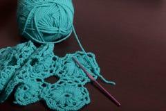 crochet Op dark ligt de oppervlakte van de lijst een onvolledig gebreid product met breinaalden en een bal van smaragdgroen-gekle Stock Afbeeldingen