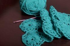 crochet Op dark ligt de oppervlakte van de lijst een onvolledig gebreid product met breinaalden en een bal van smaragdgroen-gekle Royalty-vrije Stock Foto