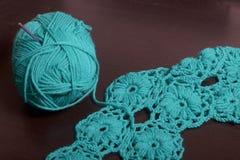 crochet Op dark ligt de oppervlakte van de lijst een onvolledig gebreid product met breinaalden en een bal van smaragdgroen-gekle stock fotografie