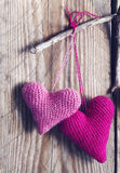 Crochet pink hearts on wooden background. Stock Images