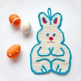 Crochet potholder Easter bunny white color with blue border and pink nose. Orange painted Easter eggs with patterns royalty free stock photography