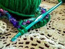 Crochet project with needle and ball of yarn stock images