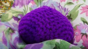 Crochet purple heart on flowery cotton material background Stock Photos