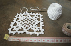 Crochet sample for tablecloth or napkin with meter. Crochet sample for tablecloth or napkin from cotton on brown wooden background Stock Images