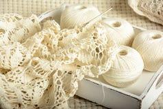 Crochet tablecloth and balls of cotton thread Stock Photos