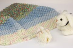Crochet work to make a baby blanket isolated on white. Little white rabbit pluche stock photography
