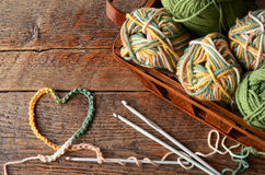 Crochet Yarn and Hook. A top view image of crochet yarn and hook with a heart shaped symbol on a wooden table top royalty free stock photography