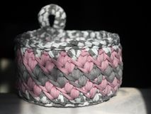 Crocheted basket crochet from knitting yarn. Multi-colored basket with loop, crocheted thick knitted yarn. Pink, white, grey, melange Royalty Free Stock Photos