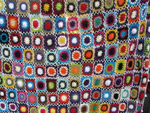 Crocheted Blanket. A brightly coloured crocheted blanket made of mutli-coloured squares stock image