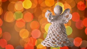 Crocheted christmas angel decoration hanging in front of blurry lights stock footage