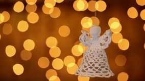 Crocheted christmas angel decoration hanging in front of xmas lights stock video footage