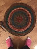 Crocheted circle rug with feet Stock Photography