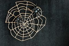 Crocheted cobweb with black rubber spiders on black velvet background. Dark halloween october concept. stock image