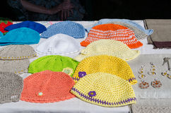 Crocheted colorful baby hat lying on stall fair Royalty Free Stock Images
