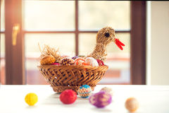 Crocheted Easter eggs and straw hen in wicker basket Royalty Free Stock Photos