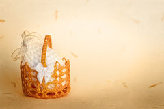 Crocheted Easter. Crocheted white easter egg in basket over handmade paper with petals texture grunge background. Shallow DOF Royalty Free Stock Photography