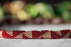 Crocheted goteó el collar del color rojo y de oro imagenes de archivo