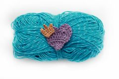 Crocheted heart with crown on the skein. Crocheted violet heart with crown on the blue skein Royalty Free Stock Images
