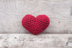 Crocheted heart on a grunge background Stock Photos