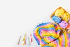 Colorful round yarn mat. Crochet. Yarn in coils and tangles. Whi. Crocheted home bright colored mat. Rainbow yarn in the basket. Hooks for knitting Royalty Free Stock Photos