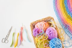 Colorful round yarn mat. Crochet. Yarn in coils and tangles. Whi. Crocheted home bright colored mat. Rainbow yarn in the basket. Hooks for knitting Stock Images