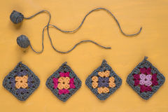 Crocheted motives on yellow background Royalty Free Stock Images