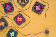 Crocheted motives on yellow background Royalty Free Stock Photography