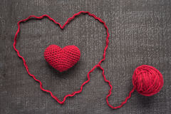 Crocheted red heart on a grunge board Stock Images
