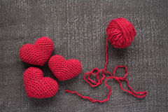 Crocheted red hearts on a grunge board Stock Photos