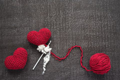 Crocheted red hearts on a grunge board Royalty Free Stock Photo