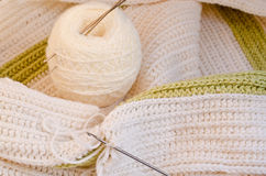 Crocheted scarf. Crochet hooks and skein on the table Stock Photo