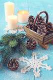 Crocheted snowflake, pine cones in basket and burning candle Royalty Free Stock Photo